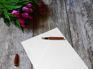 image of paper and a pen with flowers