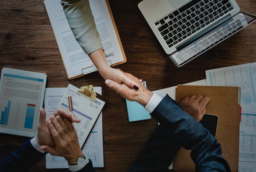 Business people shaking hands surrounded by corporate documents
